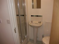 White Bathroom Suite with separate walk in shower cubicle in modern mews house for let in Bury