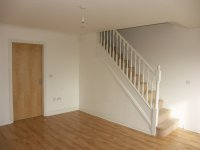 Lounge with laminated flooring and staircase off mews house for long term let in Bury