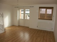 Lounge with laminated flooring and patio doors to garden in mews house for long term let in Bury